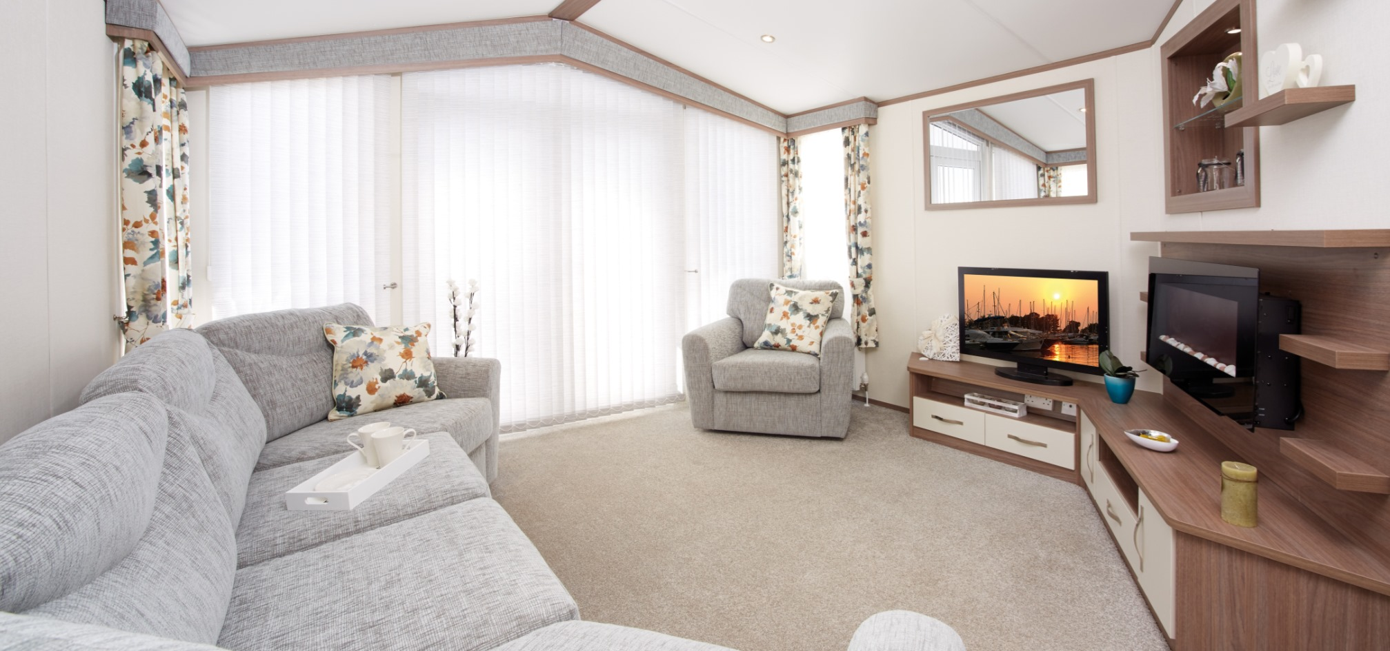 holiday home with grey sofas and colourful curtains in a spade shaped room