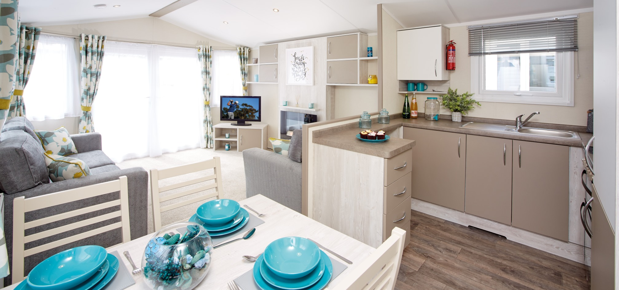wide angle view of a holiday home looking towards the living room from the dining table, with the kitchen on the right hand side.