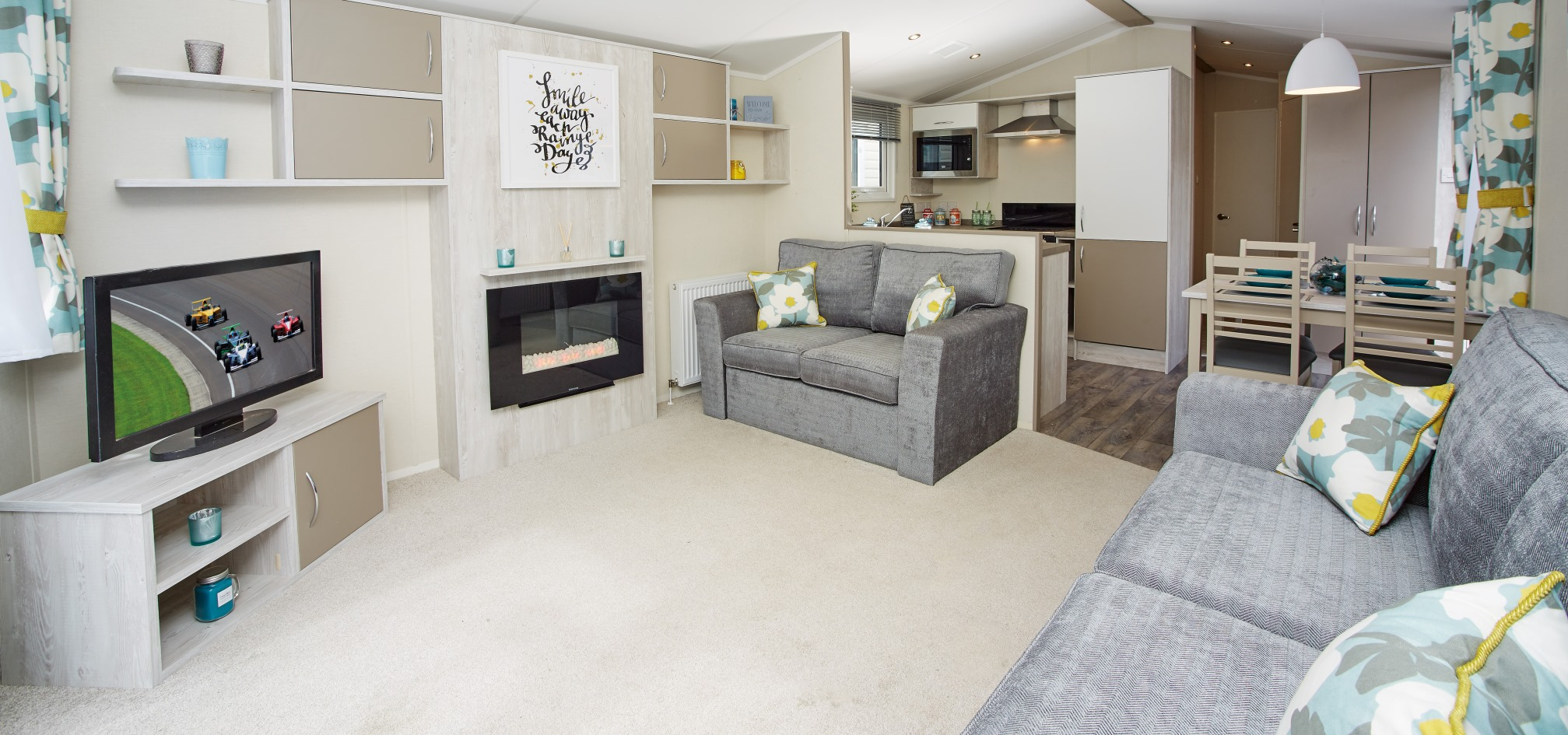 wide angle view of a holiday home with dining table, kitchen and living room in an open plan space. All nicely furnished.