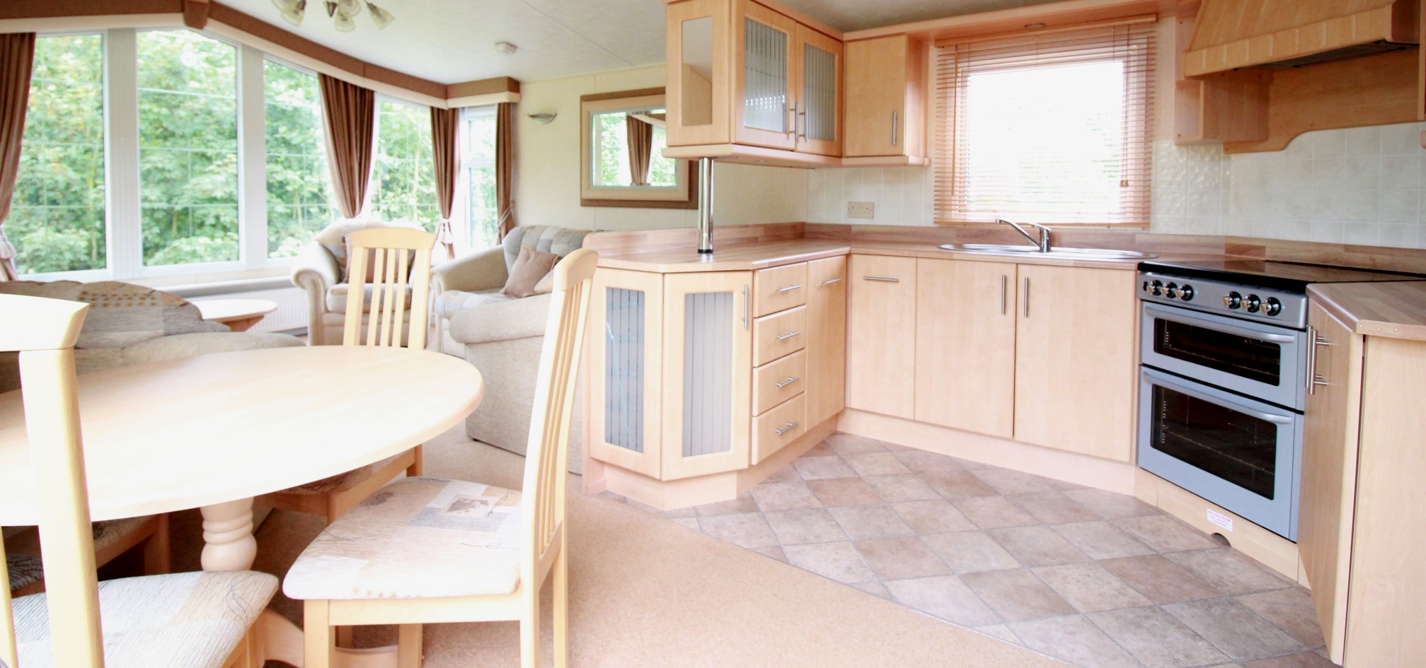 open plan living room and kitchen furnished with light brown wood throughout