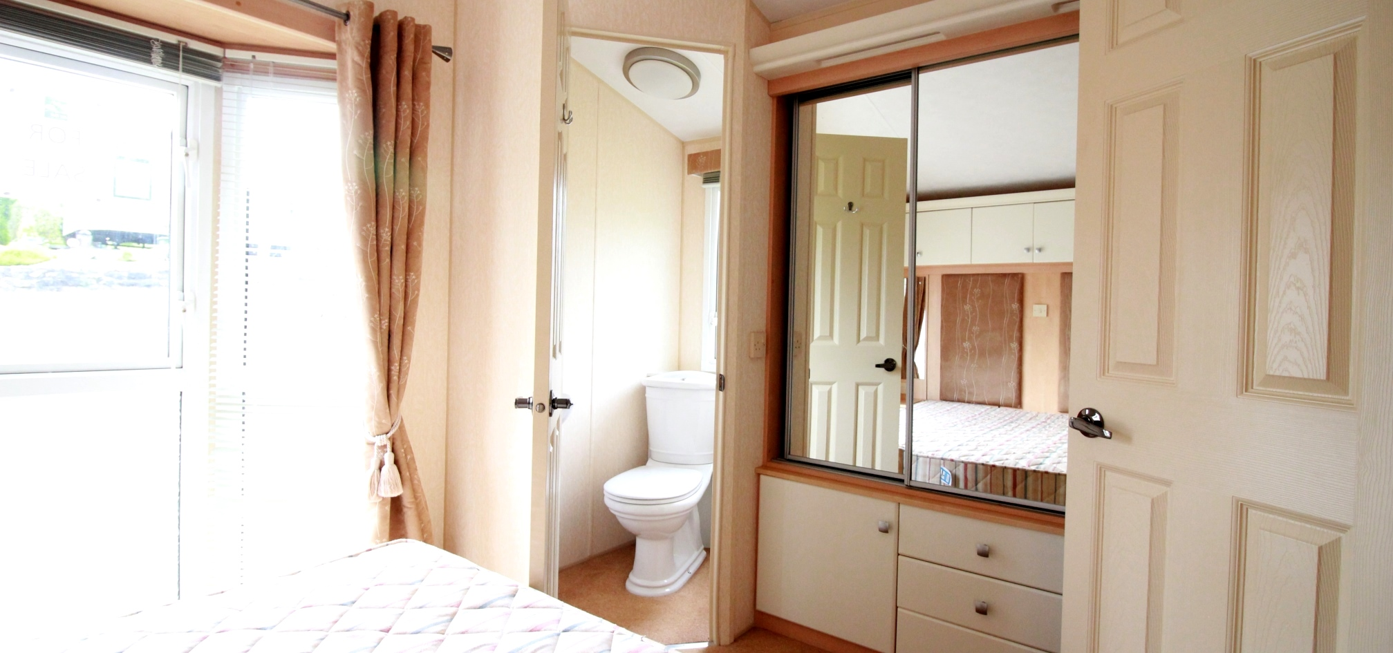 holiday home bedroom with an ensuite toilet and large windows