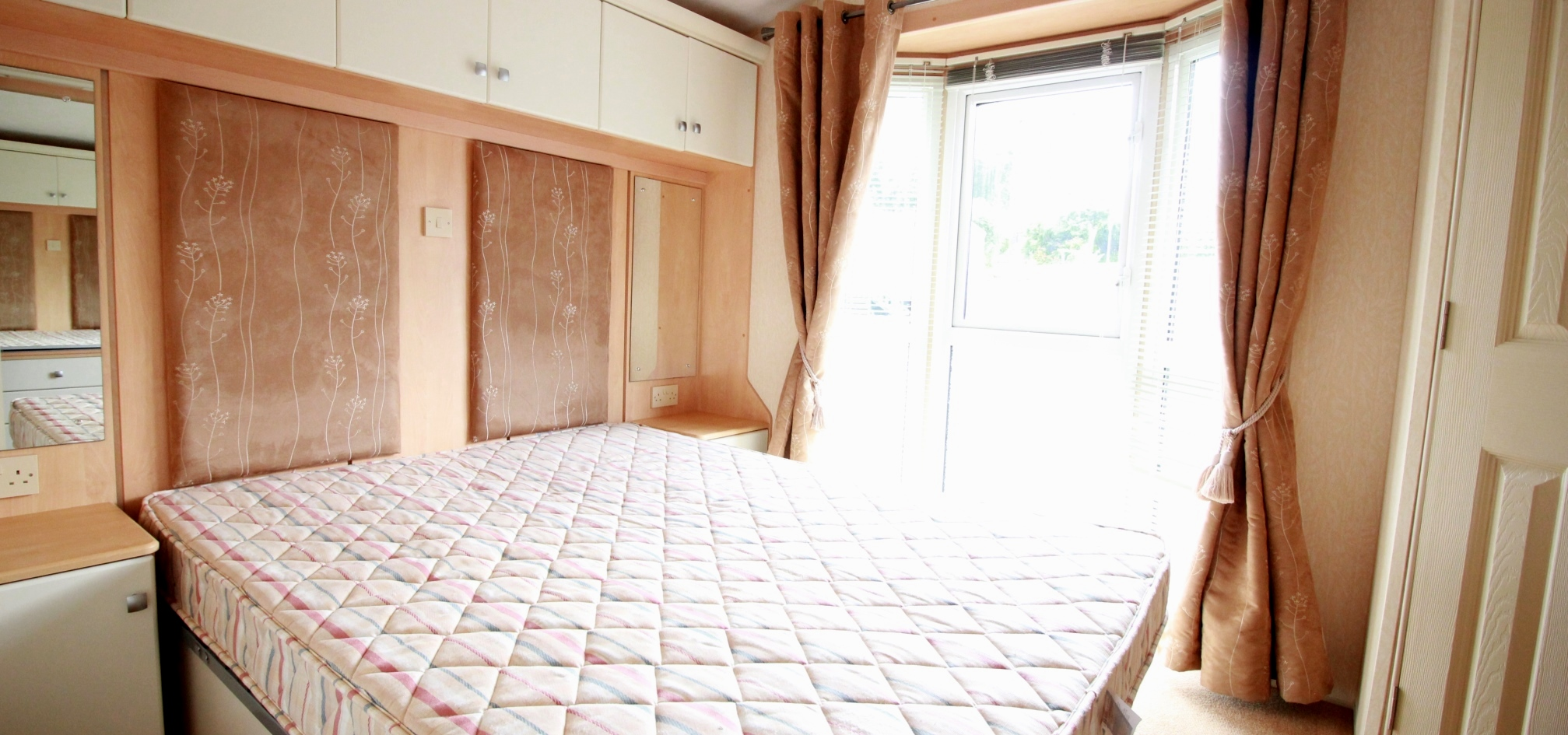 bedroom in a holiday home with a double bed and large windows