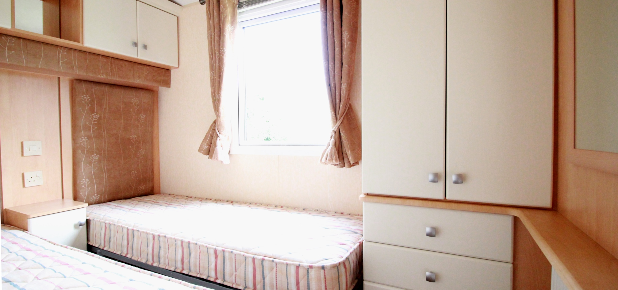 view of a twin room with identical single beds without duvets and covers