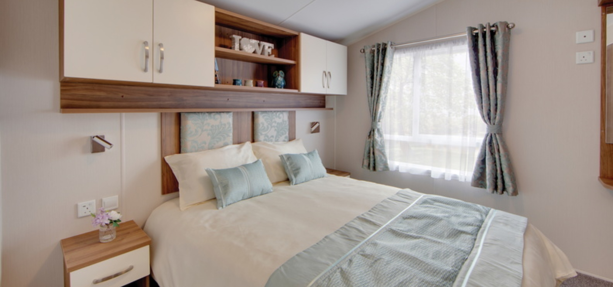 bedroom with a double bed perpendicular to a window with shelving above the bed