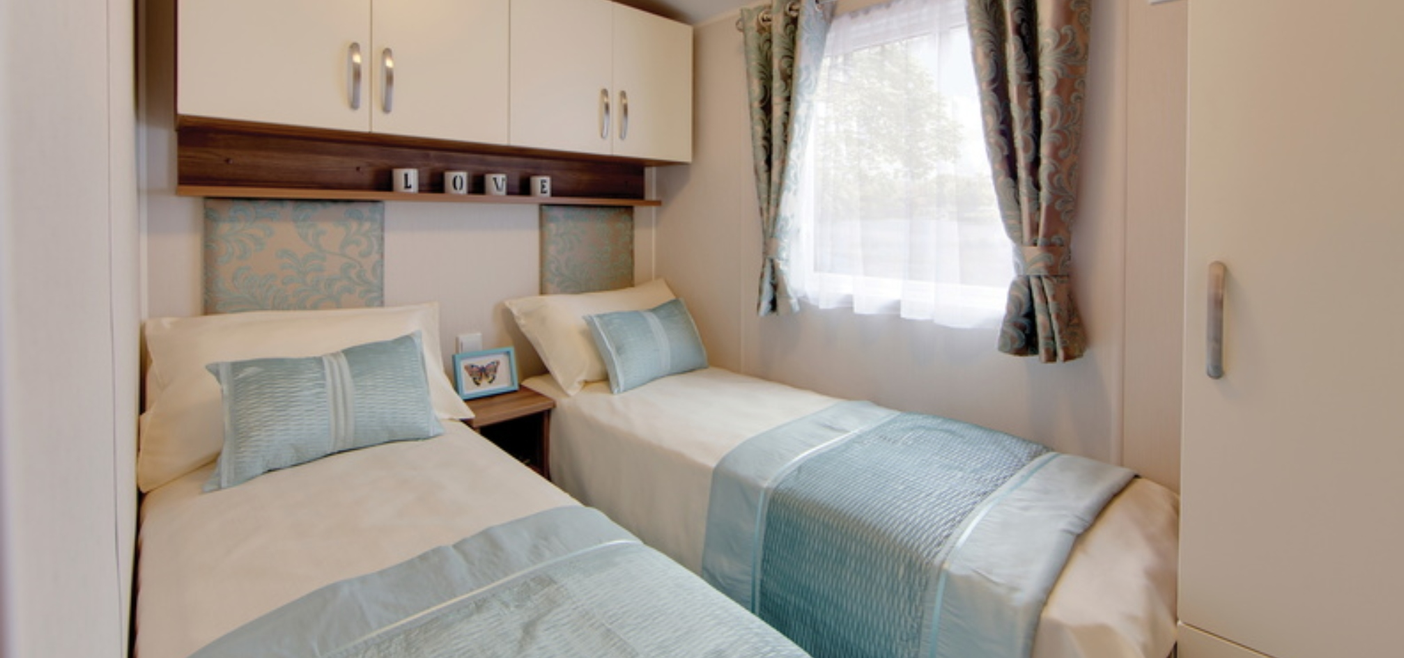 twin room with identical single beds perpendicular to a window with cupboards above the beds