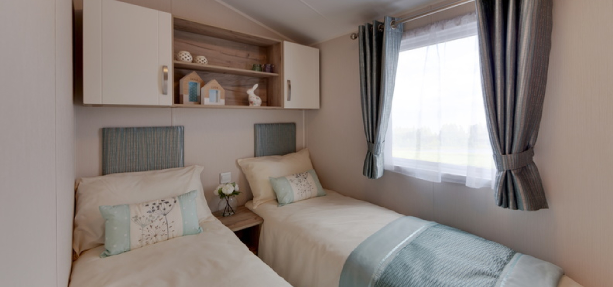a double room with twin single beds perpendicular to a window with shelving above the beds