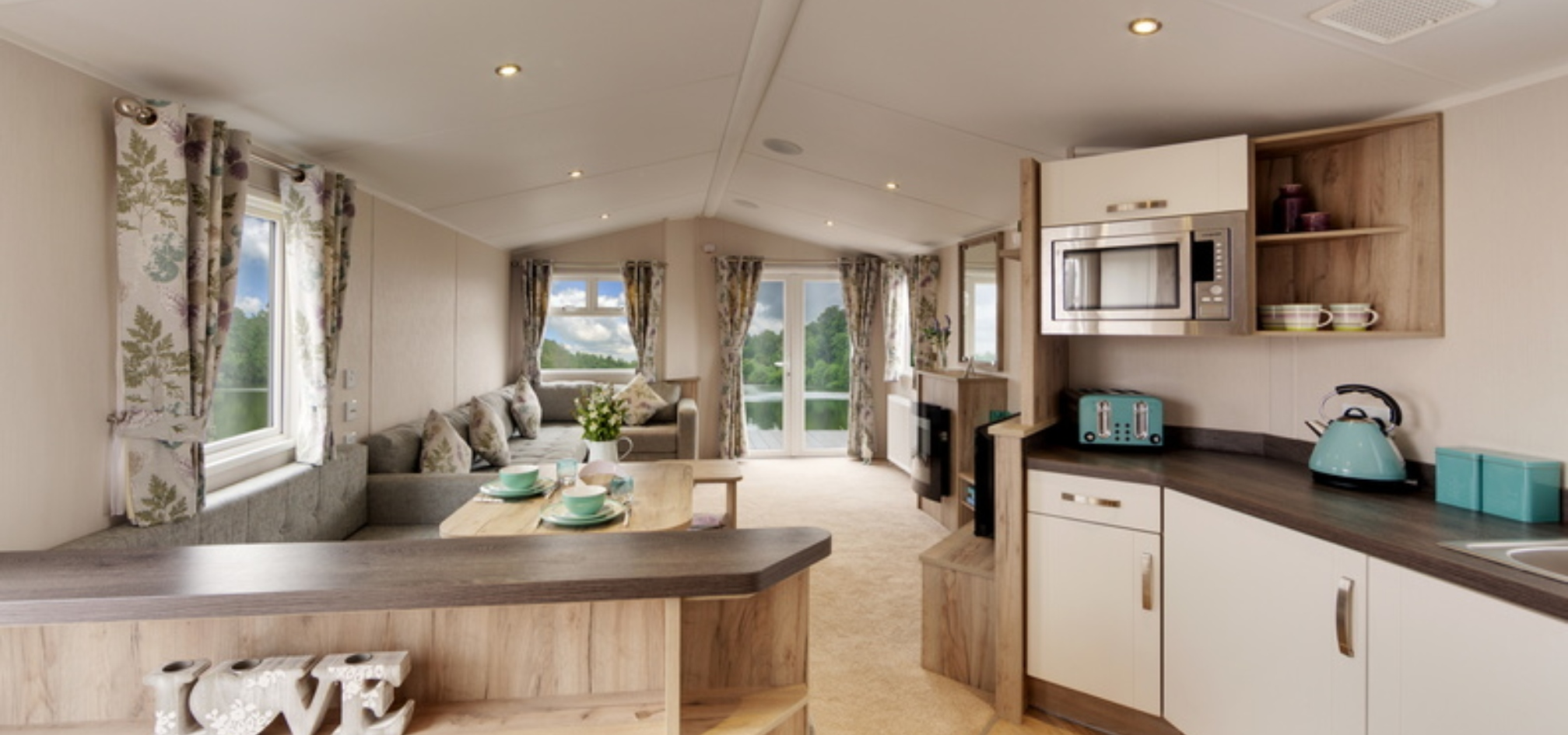 Open plan holiday home with kitchen, dining table and living room all in one large space, beautifully furnished