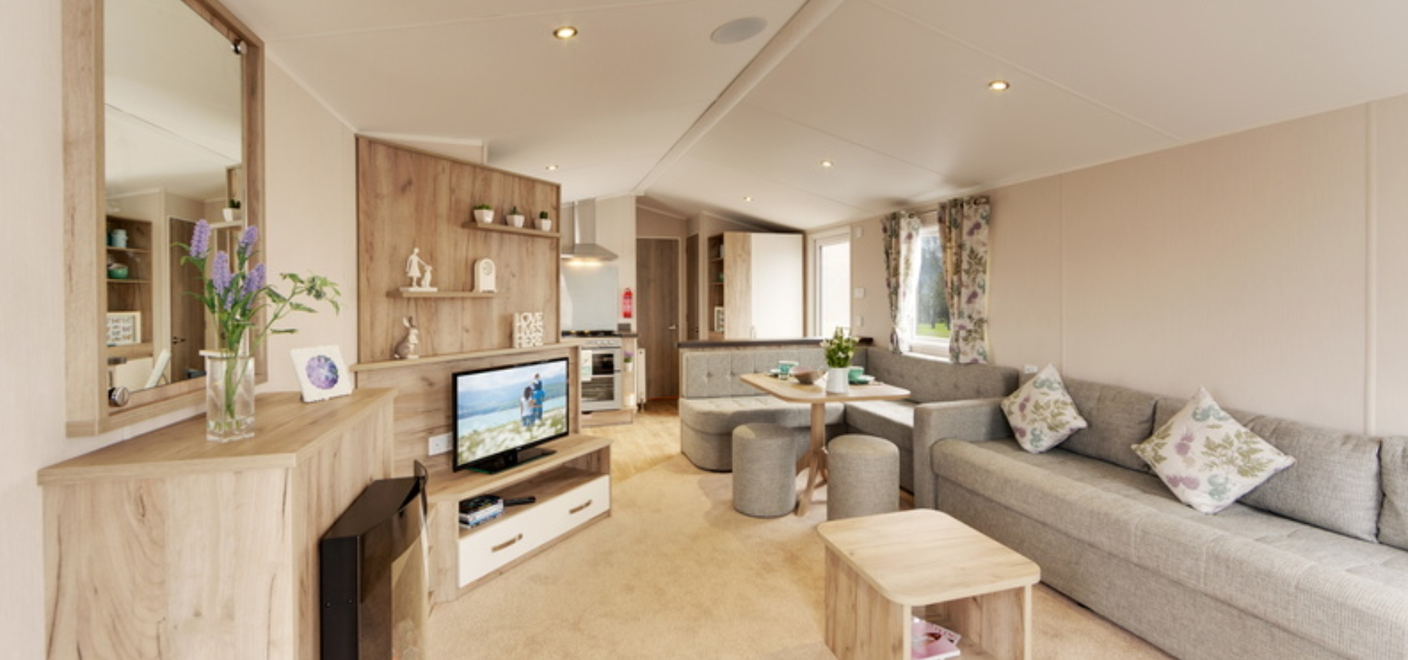 Open plan holiday home with a large living space leading into a dining area followed by a kitchen on the far left hand side