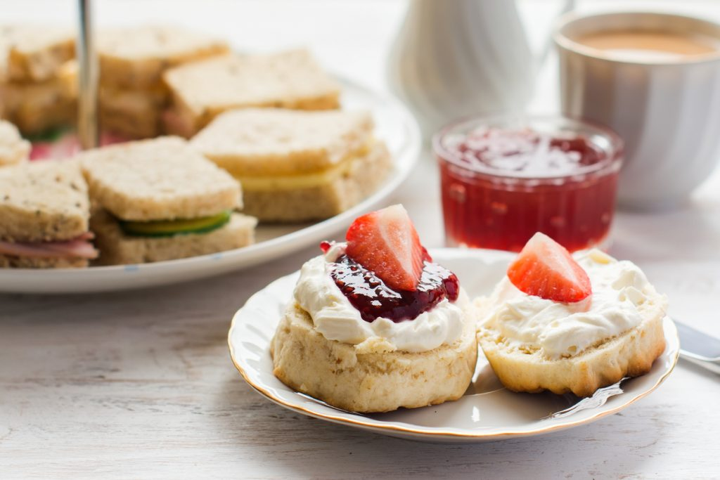 Traditional English afternoon tea: scones with clotted cream and jam, strawberries, with various sadwiches on the background, selective focus