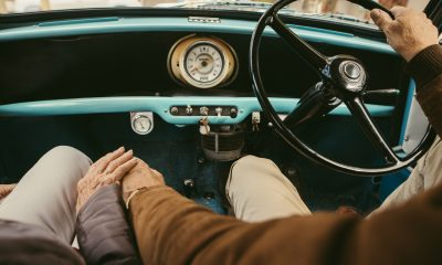 Close up of a senior couple holding hands while driving a car. Old man driving the car with woman sitting on passenger seat holding his hand.