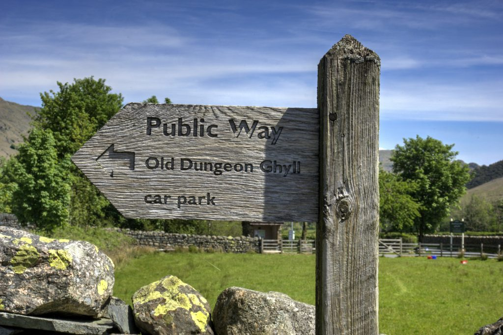 Wooden sign indicating public way and direction to Old Dungeon Ghyll
