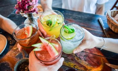 Friends toasting, saying cheers holding tropical blended fruit margaritas.