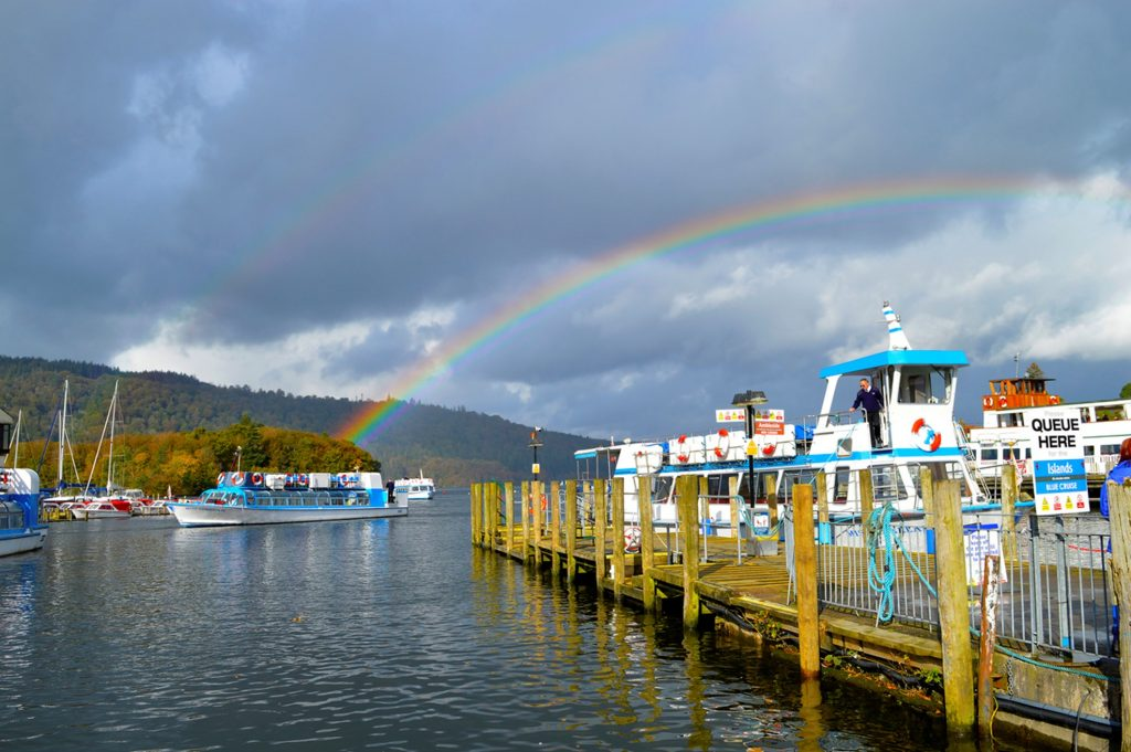 lots of boast with cloudy weather with rainbow in the backgroud